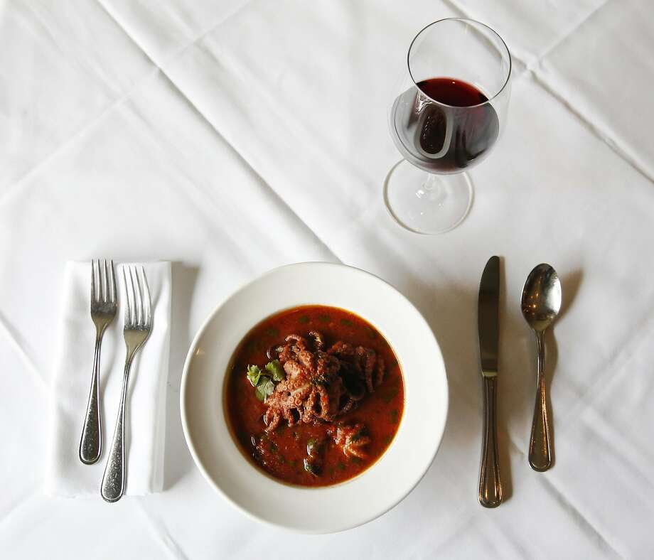 "A glass of Carignano del Sulcis ""Is Solus"" from Cantine Sardus Pater with baby octopus stew in a spicy tomato sauce at La Ciccia. Photo: Leah Millis, The Chronicle"