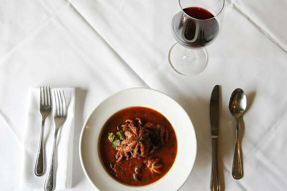A glass of Is Solus, Carignano del Sulcis with Prupisceddu in Umidu cun Tomatiga  (baby octopus stew in a spicy tomato sauce) pictured at La Ciccia May 26, 2017 in San Francisco, Calif.