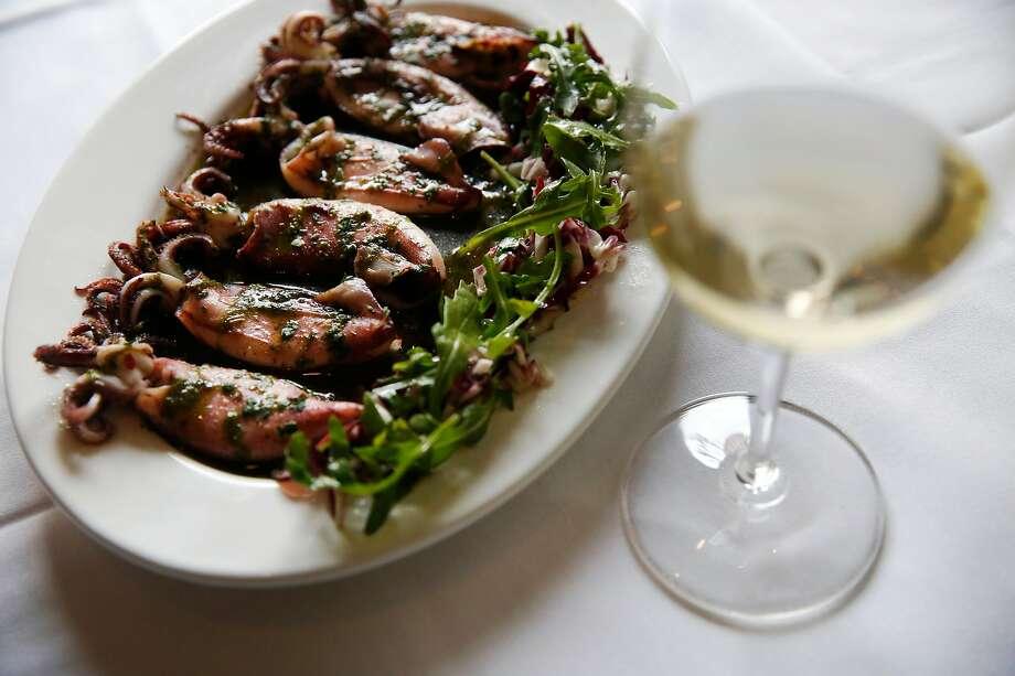 A glass of Cantine Sardus Pater Lugore Vermentino di Sardegna with a calamari appetizer at La Ciccia. Photo: Leah Millis, The Chronicle