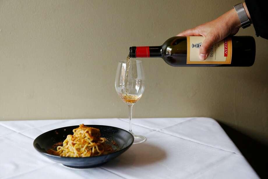 At La Ciccia, co-owner Lorella Degan pours Vernaccia di Oristano, a Sardinian wine, alongside spaghetti with bottarga. Photo: Leah Millis / The Chronicle