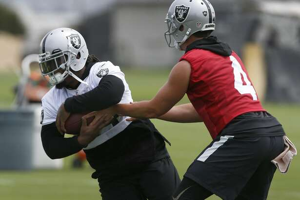 Running back Marshawn Lynch and quarterback Derek Carr practice a running play during an Oakland Raiders team workout in Alameda, Calif. on Tuesday, May 30, 2017.