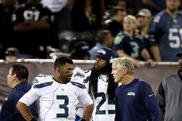 OAKLAND, CA - SEPTEMBER 01:  Head coach Pete Carroll of the Seattle Seahawks talks to Russell Wilson #3 and Richard Sherman #25 during their preseason game against the Oakland Raiders at the Oakland Alameda County Coliseum on September 1, 2016 in Oakland, California.  (Photo by Ezra Shaw/Getty Images)