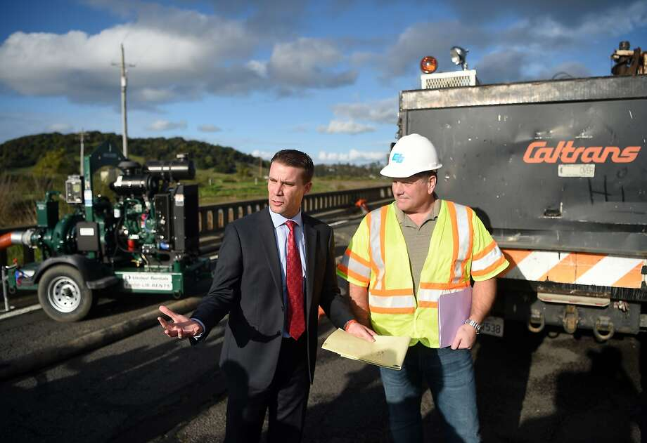 State Sen. Mike McGuire, D-Healdsburg (left), gets a briefing from Will Hauke, regional manager for Caltrans, about listens as State Senator Mike McGuire D- Healdsburg (L) speaks about a flooded section of Highway 37 in Novato, California on February 10, 2017. The road has been closed at least 14 days this winter due to flooding and extensive rain. Photo: Josh Edelson, JOSH EDELSON / SAN FRANCISCO CHRONICLE