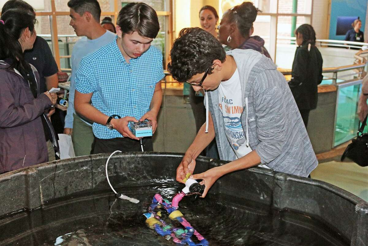 Michael Suarez, left, a freshman at Norwalk High School, and Max Parizot, a freshman at Brien McMahon High School, prepare to demonstrate their underwater remotely operated vehicle (ROV) during the May 24 end-of-year celebration for teens participating in the TeMPEST after-school program at The Maritime Aquarium at Norwalk.