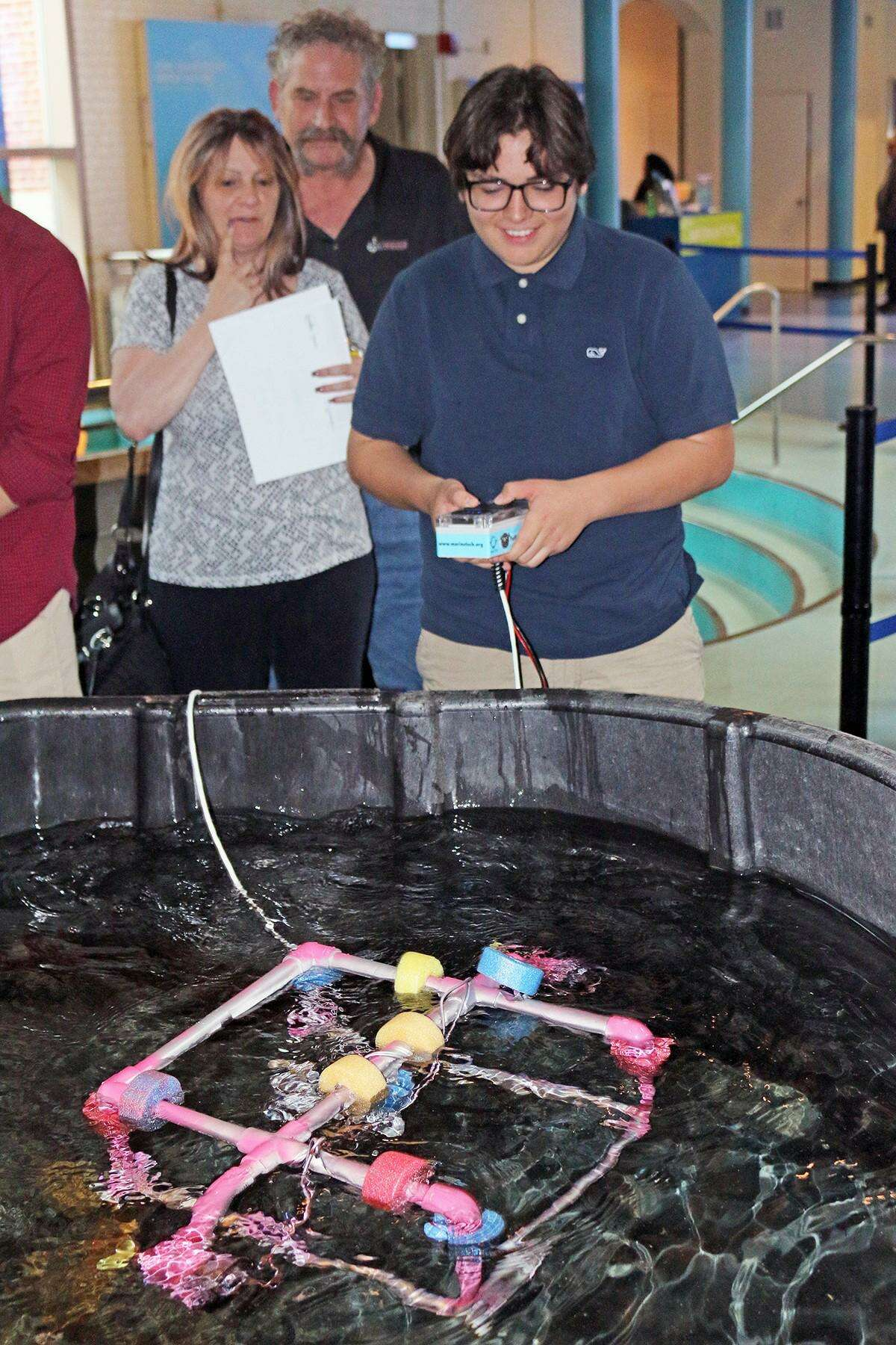 Angel Espana, a sophomore at Norwalk High School, demonstrates his underwater remotely operated vehicle (ROV) during the end-of-year celebration of the TeMPEST program May 24 at The Maritime Aquarium at Norwalk.