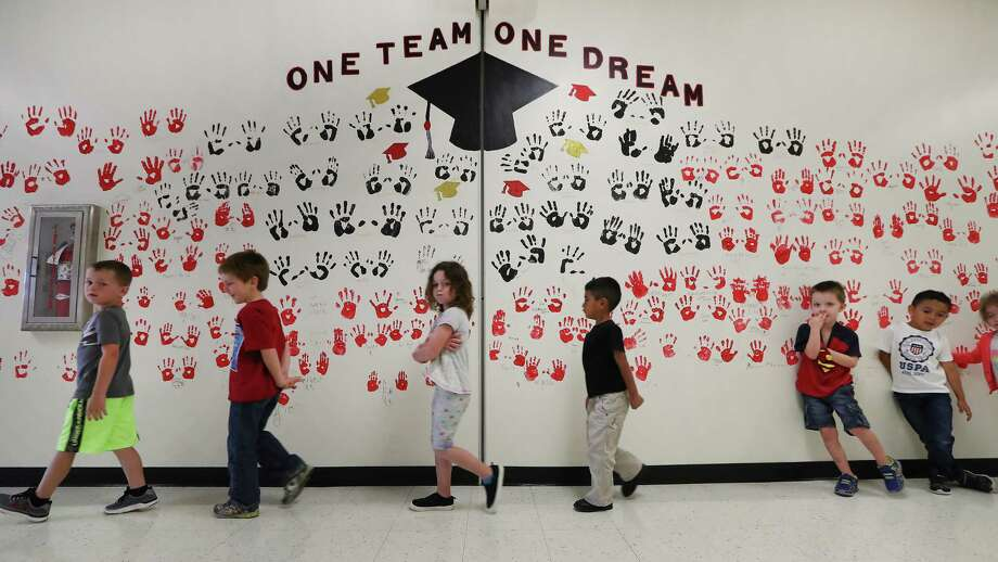 Crenshaw Elementary School kindergartner students walk by a wall of hands to lunch Friday, May 5, 2017, in Crystal Beach. ( Steve Gonzales  / Houston Chronicle ) Photo: Steve Gonzales, Staff / © 2017 Houston Chronicle