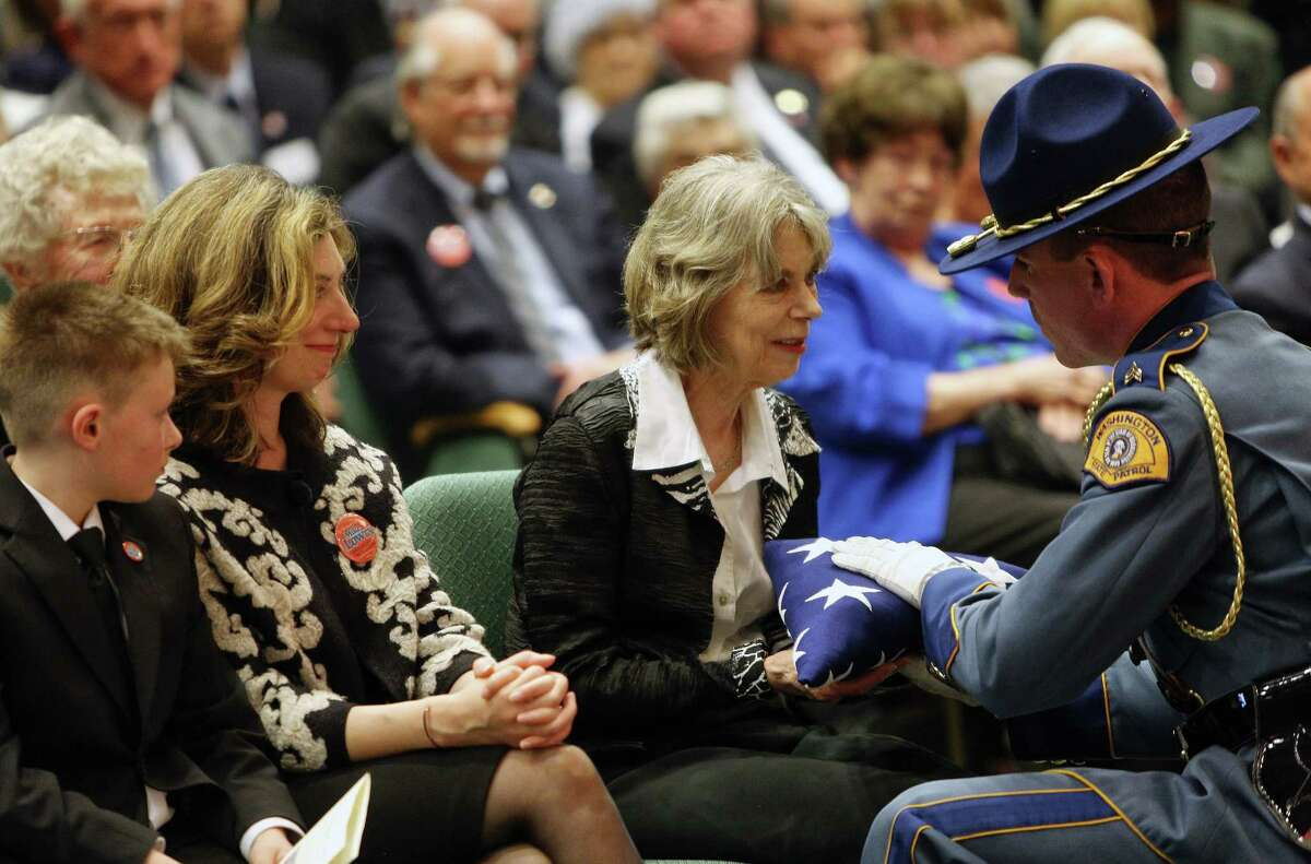 Washington State Patrol Sgt. Jason Greer hands the American Flag over to Mary Lowry, the wife of former Governor Mike Lowry, during a Celebration of Life event for Lowry, who died earlier this month, May 31, 2017, at St. Matthew's Lutheran Church in Renton.