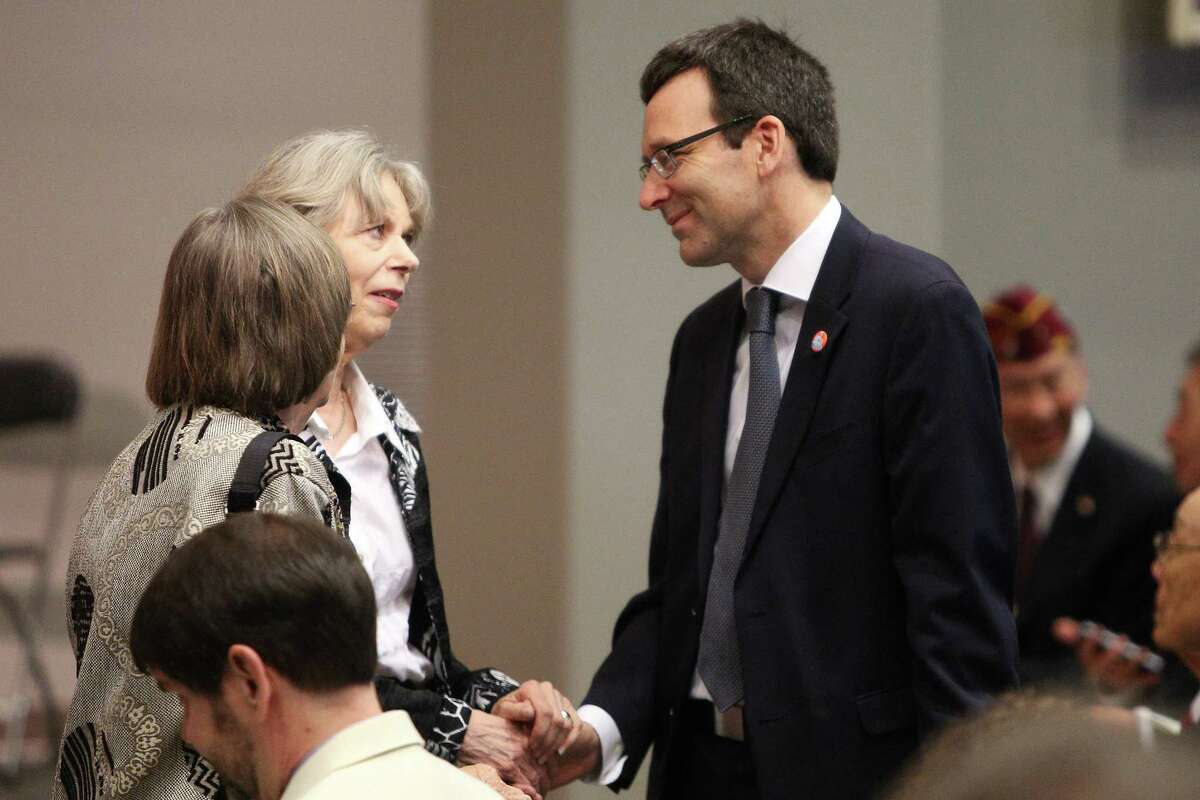 Washington State Attorney General Bob Ferguson, right, speaks with Mary Lowry, wife of former Governor Mike Lowry during a Celebration of Life event for Lowry. Ferguson and fellow Democratic attorneys general have become a major vortex of resistance to Trump administration assaults on immigrants, energy efficiency and the environment.