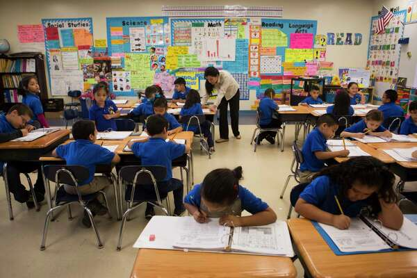 Houston Gateway Academy kindergarten teacher Miriam Del Bosque helps a student with reading comprehension material.