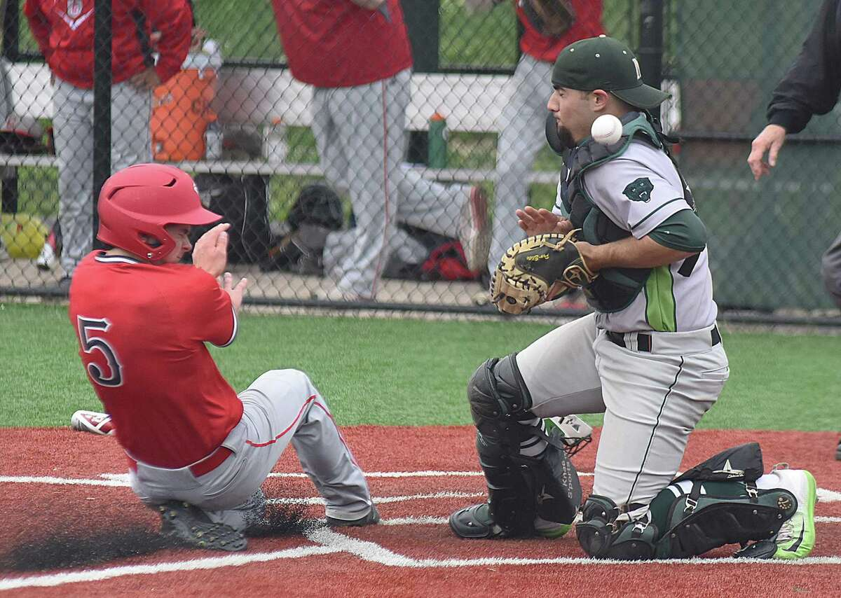 Norwalk catcher Marco Monteiro, right, can't come up with the ball on a play at the plate as Conard's Maxwell Main scores during the Chieftains' 8-4 win over the hosts Bears in the first round of the CIAC Class LL baseball tournament.