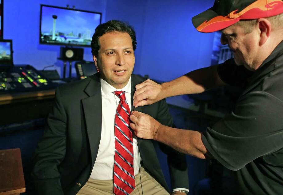 State Rep. Poncho Nevarez, D-Eagle Pass, left, has a microphone placed on him by Randy Allee, as he prepares to be interviewed by CNN from the KLRN Studios, on Tuesday, May 30, 2017.  The interview focuses on State Rep. Matt Rinaldi, R-Irving, and his comment that he had called immigration officials about protestors in the Texas House Gallery. Photo: Bob Owen, Staff / San Antonio Express-News / ©2017 San Antonio Express-News
