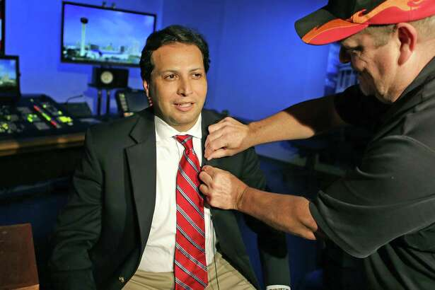 State Rep. Poncho Nevárez, D-Eagle Pass, left, has a microphone placed on him by Randy Allee, as he prepares to be interviewed by CNN from the KLRN Studios on May 30. Nevárez and fellow Democratic legislators on Wednesday called for a ban on open carrying of long guns, including rifles and shotguns, in the wake of the Sunday massacre in Sutherland Springs.
