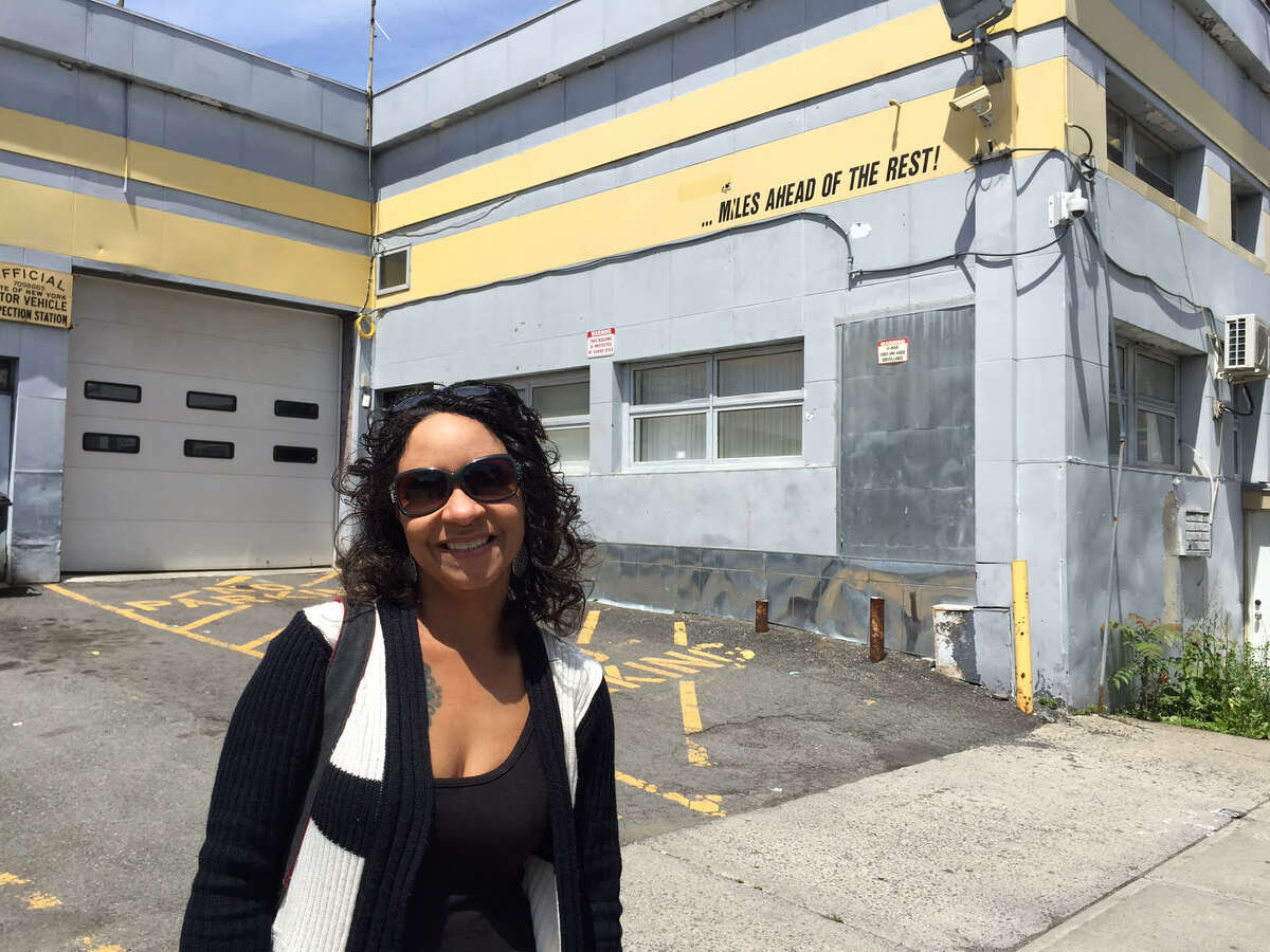 Candacy Taylor poses in front of 137 Lark St., which was listed as the Ten Eyck service station in the 1947 Green Book, which catered to African-American motorists. It is now a maintenance facility for Advantage Transit Group and Albany Yellow Cab. (Paul Grondahl / Times Union)