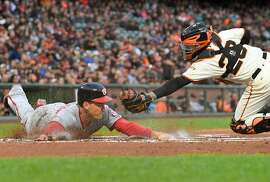 SAN FRANCISCO, CA - MAY 30:  Ryan Zimmerman #11 of the Washington Nationals scores sliding past the tag of Buster Posey #28 of the San Francisco Giants in the top of the first inning at AT&T Park on May 30, 2017 in San Francisco, California.  (Photo by Thearon W. Henderson/Getty Images)