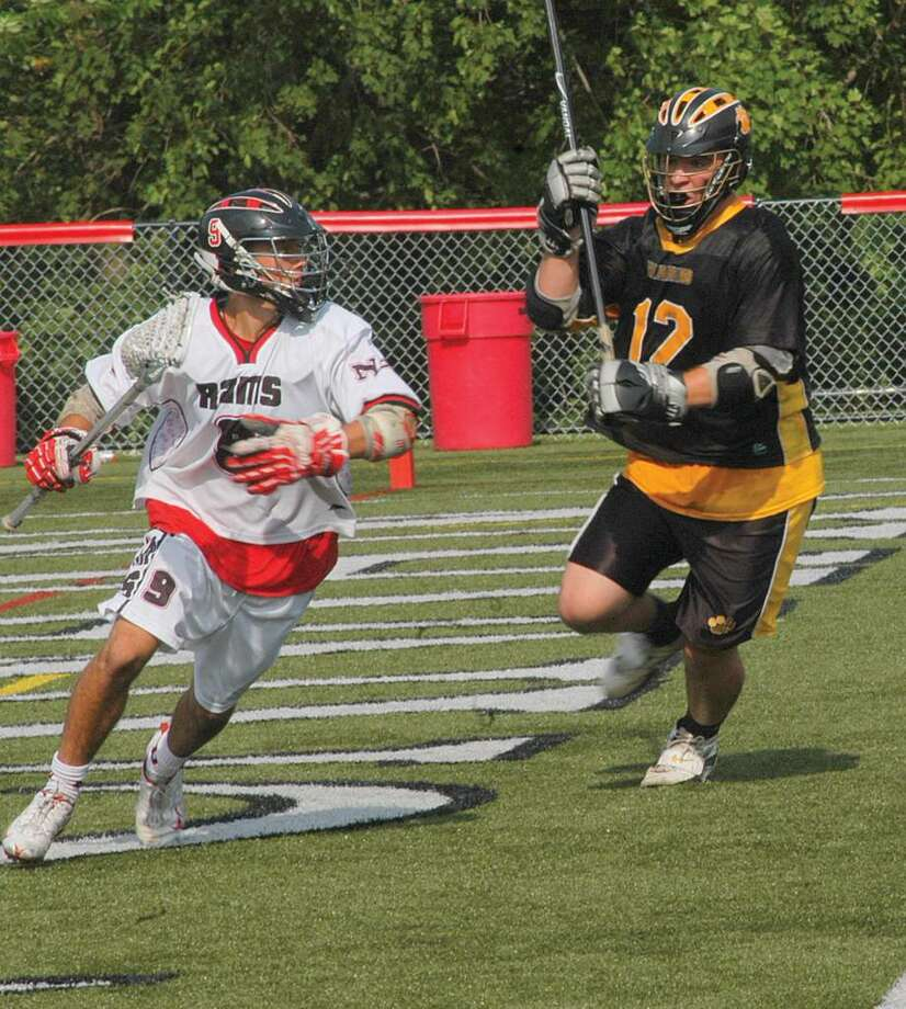 Henry Eschricht makes a move as he works his away around to the front of the Hand goal. Hand's Anthony Hill defends the play. Photo: Andy Hutchison / For The New Canaan News, Contributed Photo / New Canaan News