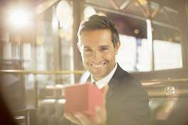 Well-dressed man holding jewelry box in restaurant