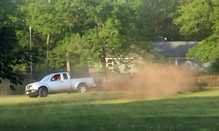 Milford Police are looking for the driver of a silver Nissan pickup truck caught on camera doing doughnuts in a baseball field on May 21, 2017. Police say the driver also ran down a bicyclist, who was not hurt. Photo: Contributed Photo / Milford Police / Contributed Photo / Connecticut Post