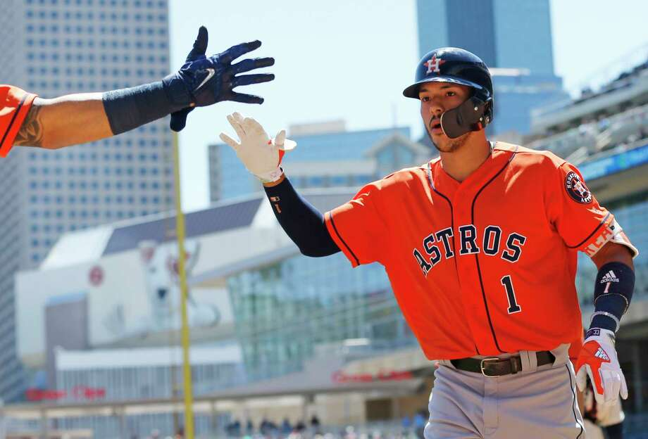 Houston Astros' Carlos Correa reaches for a congratulatory hand after he scored on his two-run home run off Minnesota Twins pitcher Hector Santiago in the first inning of a baseball game Wednesday, May 31, 2017 in Minneapolis. (AP Photo/Jim Mone) Photo: Jim Mone, Associated Press / Copyright 2017 The Associated Press. All rights reserved.