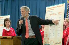 Professor Robert Pollin, a researcher from the University of Massachussetts-Amherst, gestures to a chart showing estimates of cost savings if a proposed single-payer health care bill was approved by the Legislature, during a news conference, Wednesday, May 31, 2017,in Sacramento, Calif. A report released by the California Nurses Association, done by Pollin and others, suggests that a 2.3 precent sales tax and a 2.3 precent gross receipts tax would help cover the additional costs to provide health care for all Californians.