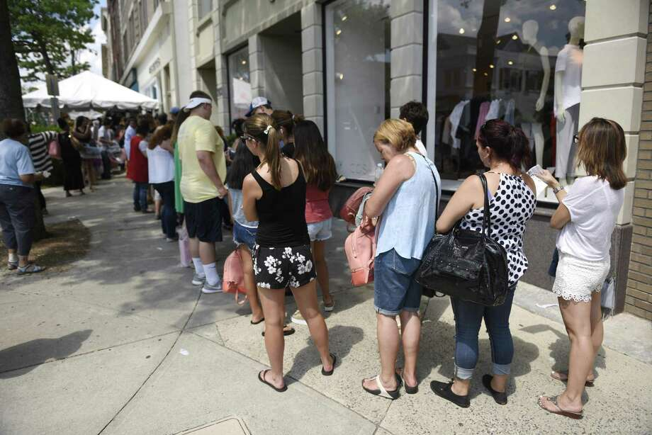 Dozens of people wait in July 2016 outside Michael Kors in Greenwich, Conn, to purchase discount designer handbags during the Greenwich Chamber of Commerce Sidewalk Sale Days. On May 31, 2017, Michael Kors announced plans to close at least 120 stores, without immediately specifying locations. Photo: Tyler Sizemore / Hearst Connecticut Media / Greenwich Time