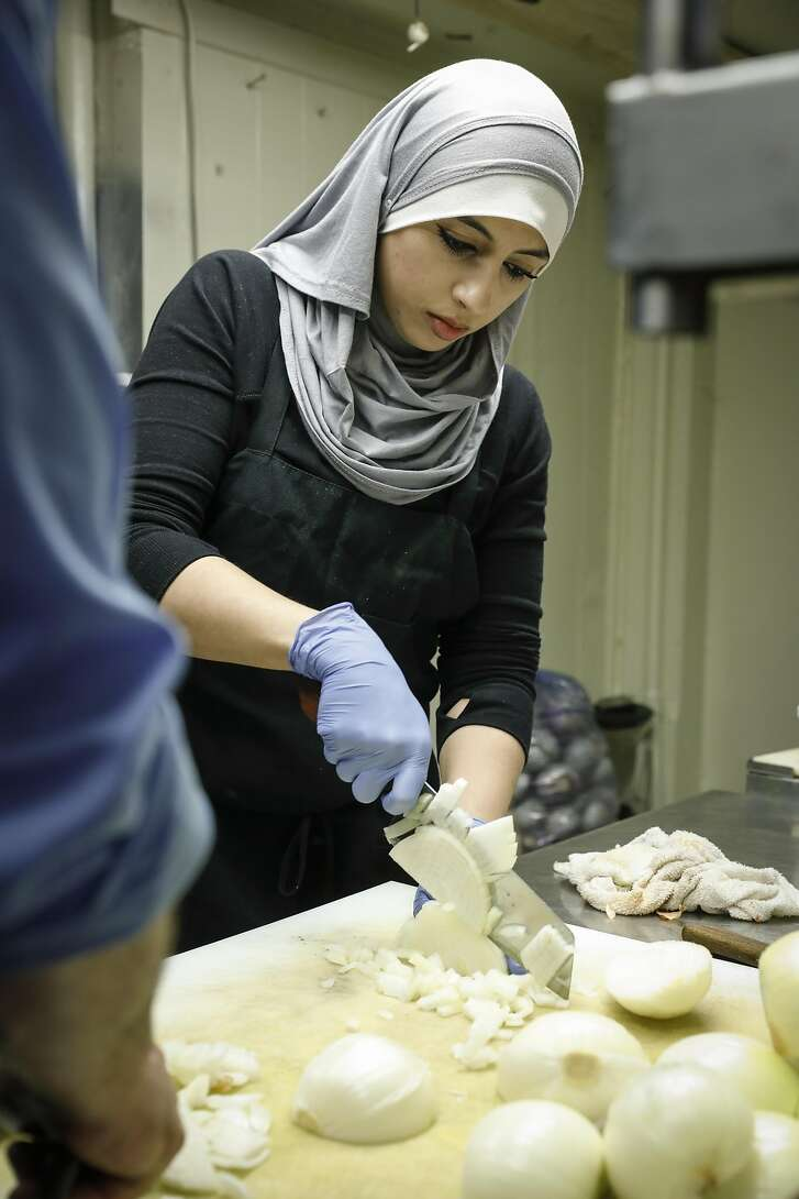 Chef Tahani Mohammad chops onions while preparing Musakhan in the kitchen at Old Jerusalem Restaurant on Tuesday, May 23, 2017 in San Francisco, Calif.