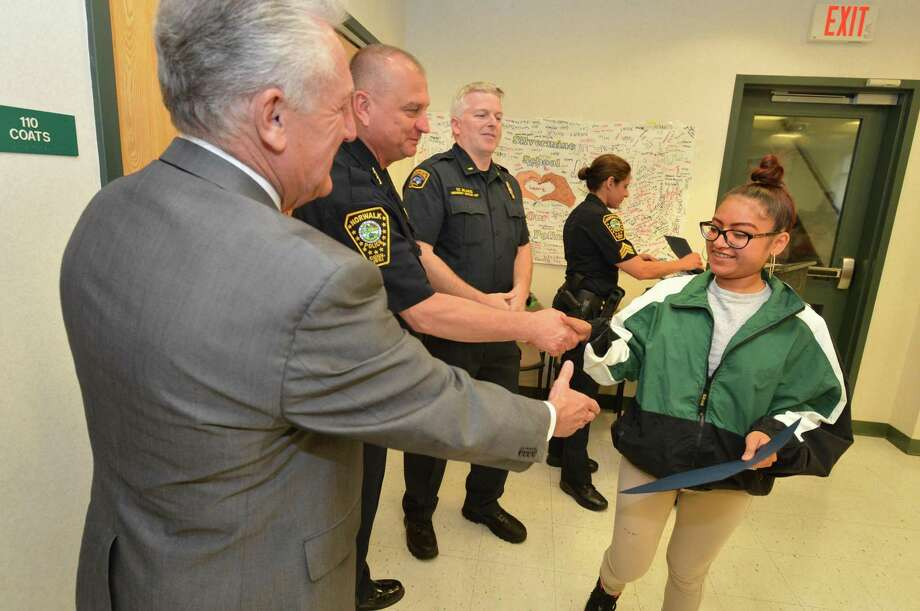 Scarlet Sanchez is congratulated by Norwalk Police Chief Tom Kulawik and Mayor Harry Rilling and others as she accepts her certificate for completeion of the Justice and Law Academy at police heaquarters on Wednesday May 31, 2017 in Norwalk Conn. Pathways Academy graduated almost two dozen students from the four month justice and fire programs. Photo: Alex Von Kleydorff / Hearst Connecticut Media / Norwalk Hour