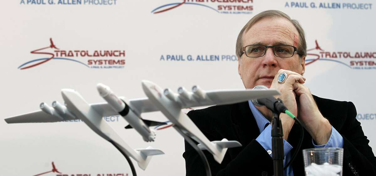 Microsoft co-founder Paul Allen looks across at a model of a giant airplane and spaceship he plans on building, during a news conference about the plane, Tuesday, Dec. 13, 2011, in Seattle. Allen and aerospace pioneer Burt Rutan announced they're building a giant airplane and spaceship to zip people and cargo into orbit, but unlike traditional rockets and government spaceships, the new commercial spaceship will drop from a high-flying airplane instead of blasting off from a launch pad. (AP Photo/Elaine Thompson)