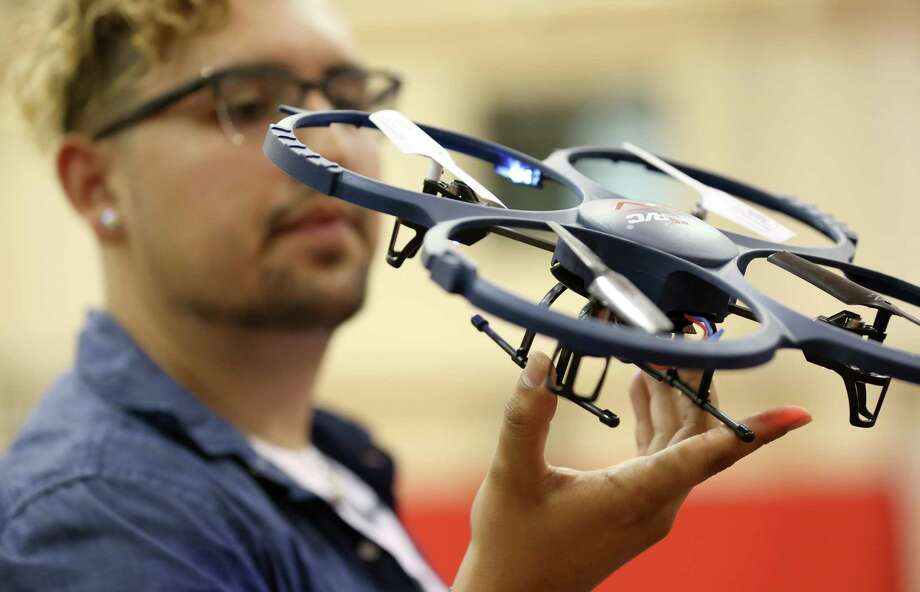 """Jose Luis Del Aguila examines a drone. """"Flying an unmanned aircraft has a lot of rules,"""" he says. Photo: Godofredo A. Vasquez, Staff / Godofredo A. Vasquez"""