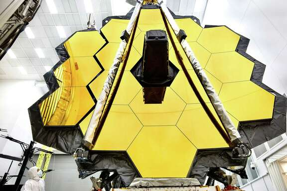 "This NASA photo released on May 16, 2017 shows the primary mirror of NASAs James Webb Space Telescope inside a cleanroom at NASAs Johnson Space Center in Houston,Texas where it will undergo its last cryogenic test before it is launched into space in 2018.   In preparation for testing, the wings of the mirror (which consist of the three segments on each side) were spread open.  This photo shows one fully deployed wing, and one that is moments from being fully deployed. An engineer observes the move.The James Webb Space Telescope is the worlds most advanced space observatory. It is designed to unravel some of the greatest mysteries of the universe, from discovering the first stars and galaxies that formed after the big bang to studying the atmospheres of planets around other stars.  / AFP PHOTO / NASA / Chris GUNN / RESTRICTED TO EDITORIAL USE - MANDATORY CREDIT ""AFP PHOTO / NASA/CHRIS GUNN"" - NO MARKETING NO ADVERTISING CAMPAIGNS - DISTRIBUTED AS A SERVICE TO CLIENTS  CHRIS GUNN/AFP/Getty Images"
