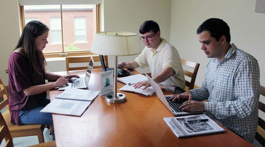 Darien High School seniors, from left, Lindsey Fagerstrom, Henry Keena and Jonathan Stimpson work at the library in Darien on May 23 creating STEM curriculum for a summer camp in Norwalk as part of their Boy Scout Venture crew. Photo: Erin Kayata / Hearst Connecticut Media / Darien News