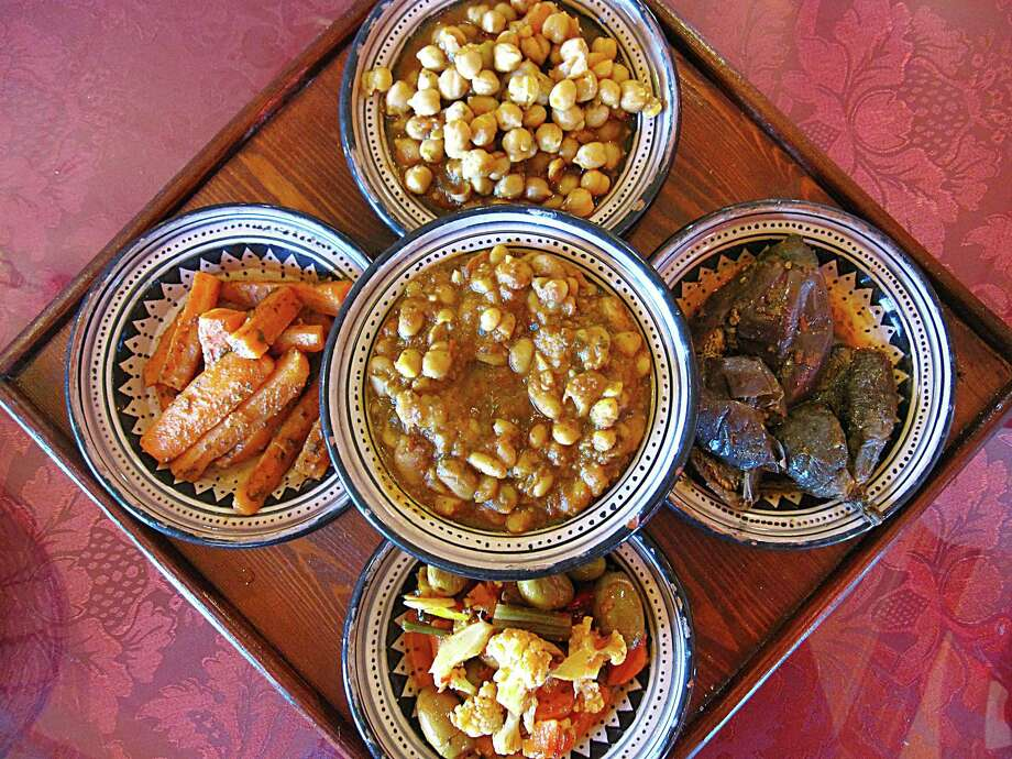 An appetizer sampler including, clockwise from left, marinated carrots, full chickpea hummus, eggplant, giardiniera and white beans, center, from Moroccan Bites Tagine. Photo: Mike Sutter /San Antonio Express-News