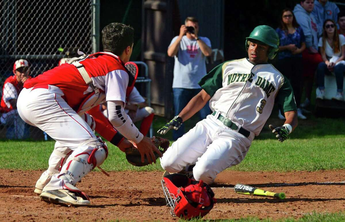 Masuk catcher Enzo Merlonghi prepares to tag out Notre Dame of West Haven's Akshay Reddy at home plate during baseball action in Monroe, Conn., on Wednesday May 31, 2017.