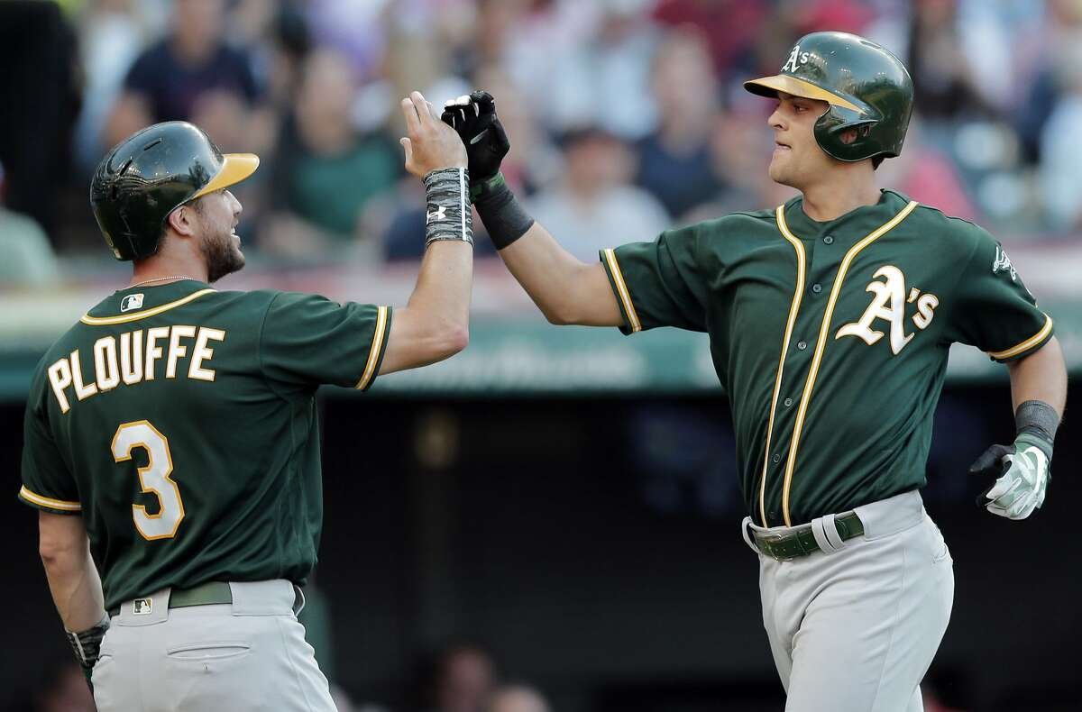 RETRANSMISSION TO CORRECT TO TW0-RUN HOME RUN - Oakland Athletics' Chad Pinder, right, is congratulated by Trevor Plouffe after Pinder hit a two-run home run off Cleveland Indians starting pitcher Mike Clevinger in the fifth inning of a baseball game, Wednesday, May 31, 2017, in Cleveland. (AP Photo/Tony Dejak)