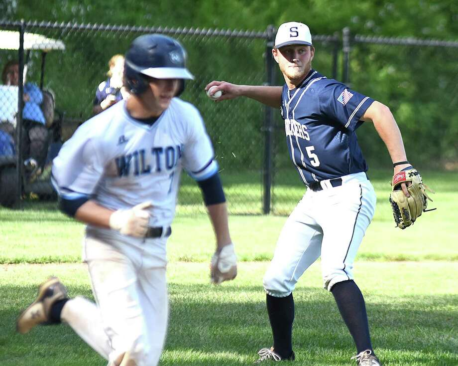 Staples pitcher Ben Casparius, right, fires to first after scooping a bunt by Wilton's Kyle Phillips, left, on a sacrifice during Wednesday's CIAC Class LL baseball tournament second-round game in Wilton. Staples won 3-0. Photo: John Nash / Hearst Connecticut Media / Norwalk Hour