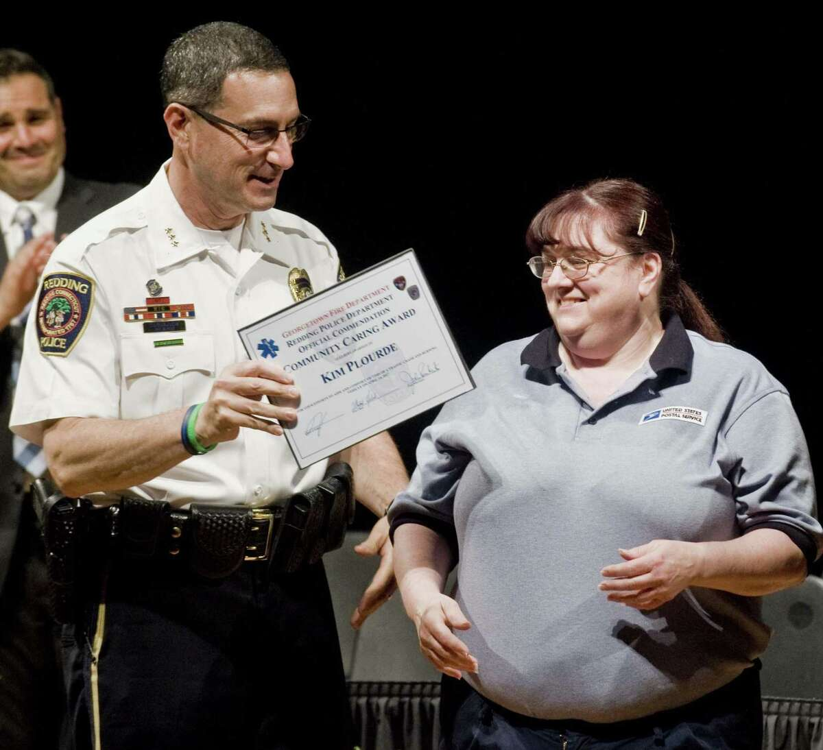 Redding Police Chief Douglas Fuchs hands Kim Plourde a Community Caring Award during the Community Recognition Ceremony at Joel Barlow High School honoring police officers, firefighters, EMS first responders as well as civilians who helped the teenagers during the fiery crash in April. Wednesday, May 31, 2017