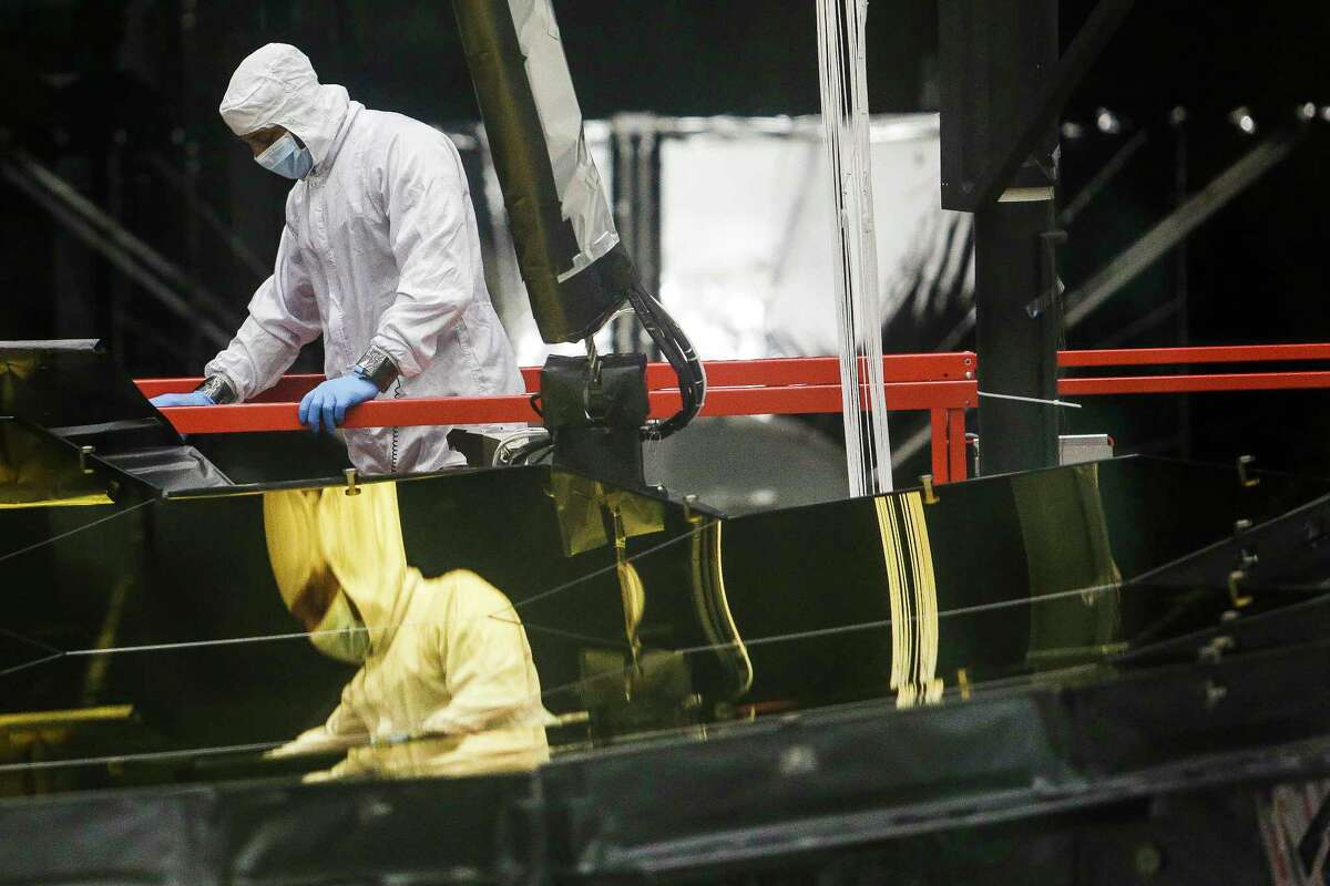 A NASA engineer is reflected in the mirrors of the James Webb Space Telescope at Johnson Space Center.