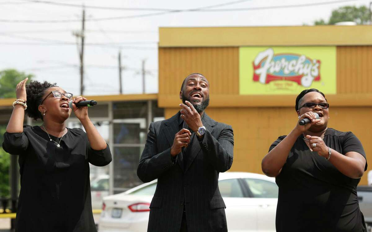 Wheeler Avenue Baptist Church's Kiana Day-Williams, left to right, Chad Bradley, and Leona Lewis sing a prayer before a press conference to announce the church's expansion to where Frenchy's Chicken currently stands Wednesday, May 31, 2017, in Houston. The restaurant will move to the intersection of Scott and Alabama streets.