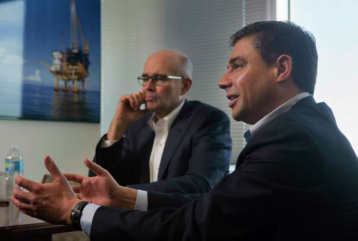 FILE - Martin Craighead (left), chairman and CEO of Baker Hughes, and Lorenzo Simonelli (right), president and CEO of GE Oil & Gas, discuss their merger deal in Houston, Texas. Experts believe the deal should close Monday morning.