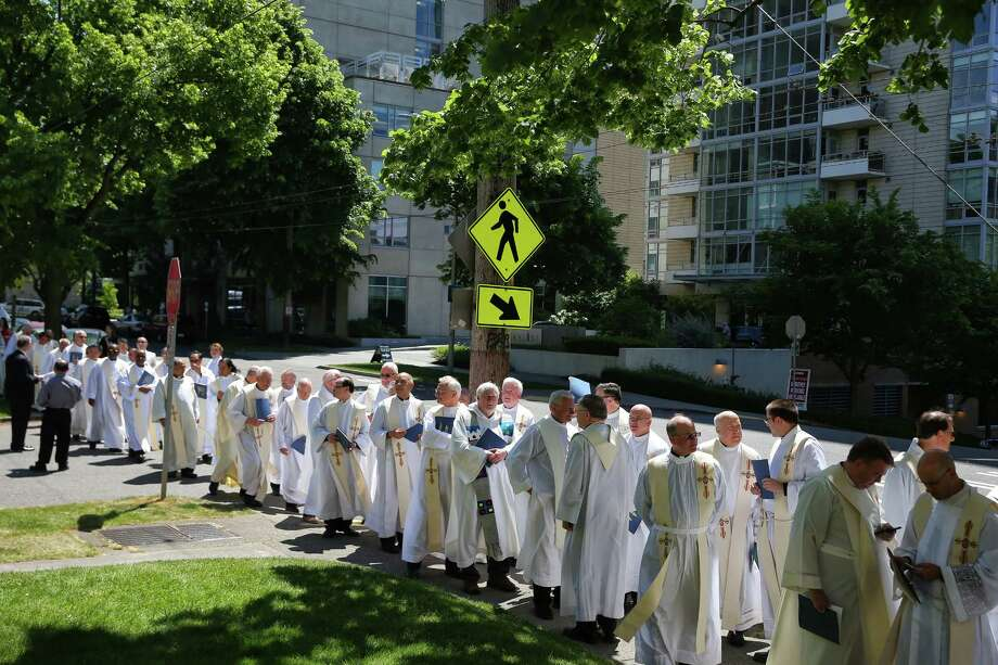 Priests line up along 9th Avenue before the ordination of Daniel H. Mueggenborg as bishop, Wednesday, May 31, 2017 at St. James Cathedral. Holy Water fonts have been removed due to the novel coronavirus. The Sign of Peace, at mass, will be a nod and verbal greeting rather than a handshake. Photo: GENNA MARTIN, SEATTLEPI.COM / SEATTLEPI.COM