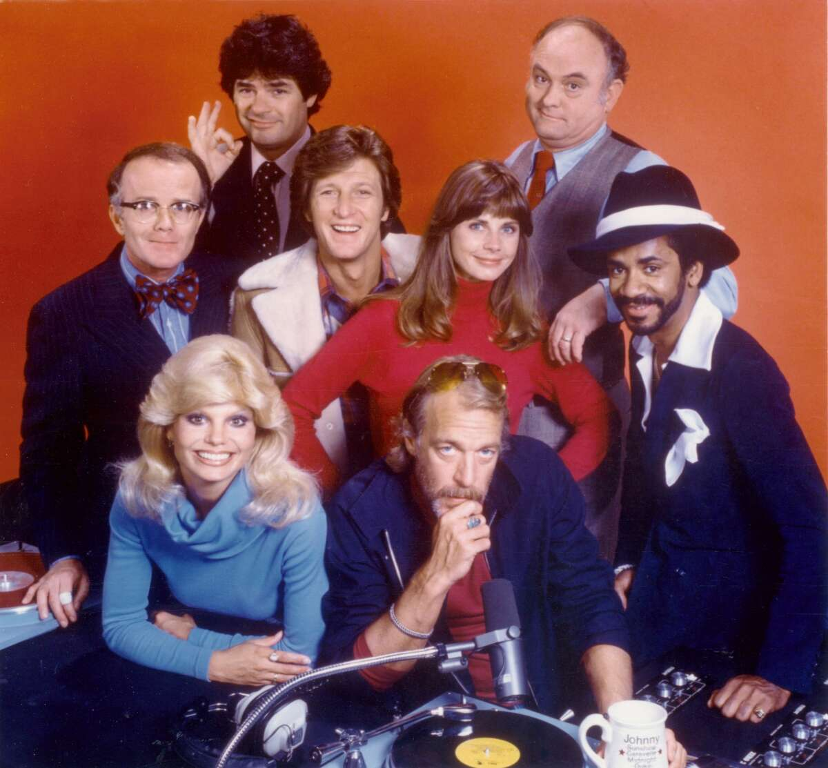 """Cast members (from left) Richard Sanders, Frank Bonner (in back), Loni Anderson, Gary Sandy, Howard Hesseman (seated in front), Jan Smithers, Gordon Jump and Tim Reid, star in the CBS television series """"WKRP in Cincinnati."""" Image dated 1979. (Photo by CBS via Getty Images)"""