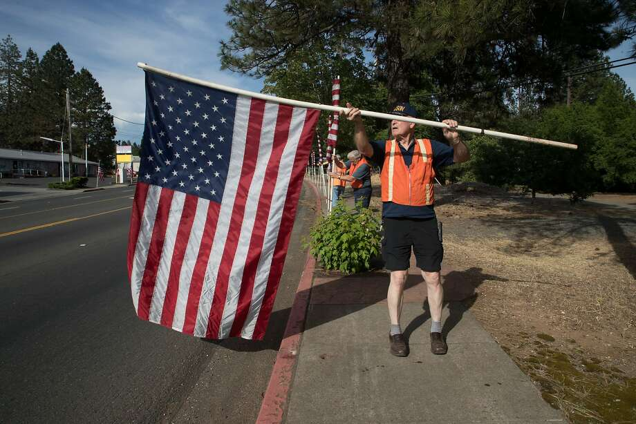 Henry Bomgardner rolls up one of 1,200 American flags lining both sides of a road in Paradise (Butte County) on Memorial Day. Photo: Paul Kuroda, Special To The Chronicle