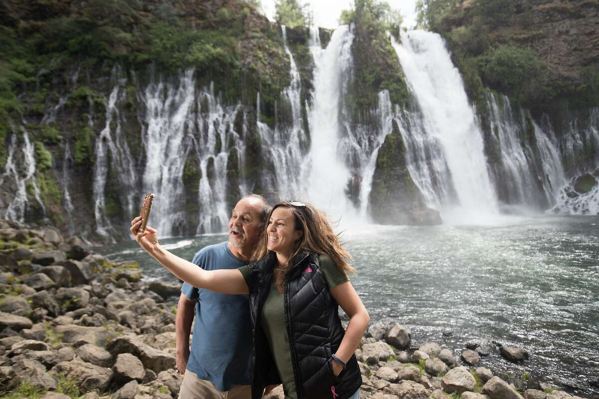 """Lois Navarro takes a photo with her dad, Raul, at the Burney Falls on Tuesday, May 30 2017, Burney, CA. Burney Falls water comes from underground springs above and at the falls, which are 129 feet high, and provides an almost constant flow rate even during the dry summer months. Tuesday, May 30 2017, Burney, CA. The falls were called """"the Eighth Wonder of the World"""" by President Theodore Roosevelt"""