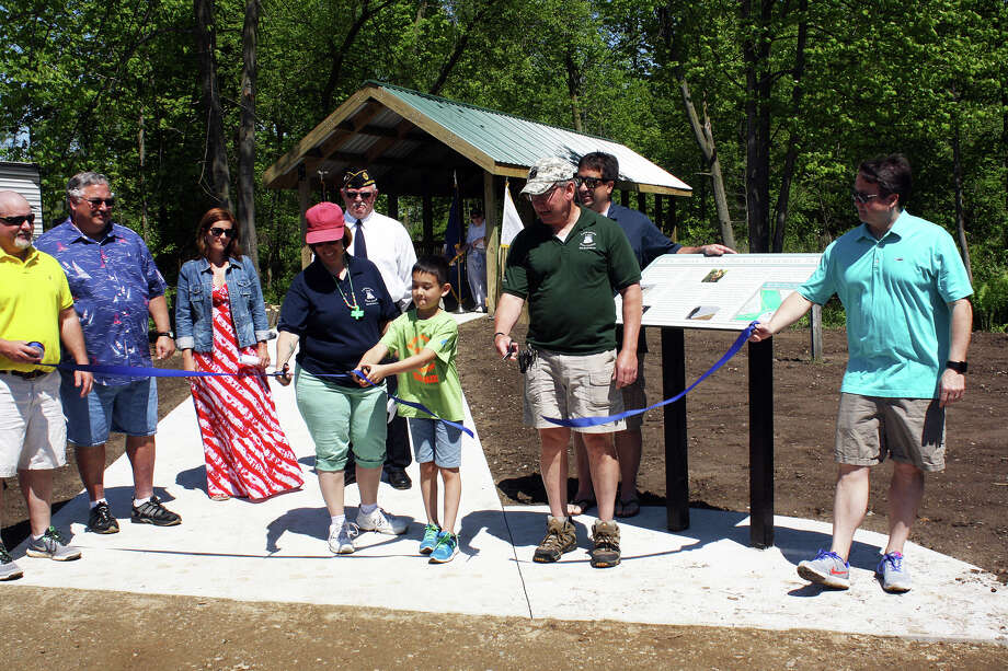 PFC Backus' mother, Ann, son Jack, and dad Al, cut the trail's ribbon Photo: Rich Harp/For The Tribune