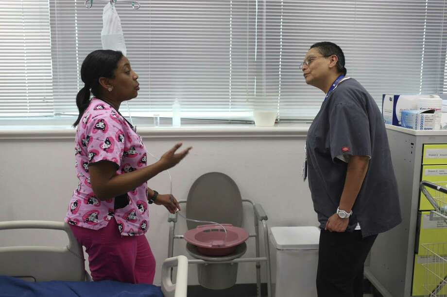 Nursing instructor Barbara Govan (left) goes over details of lab work with Elisa Delgado, a student in Project QUEST's licensed vocational nurse program at St. Philip's College. Photo: Jerry Lara /San Antonio Express-News / © 2017 San Antonio Express-News