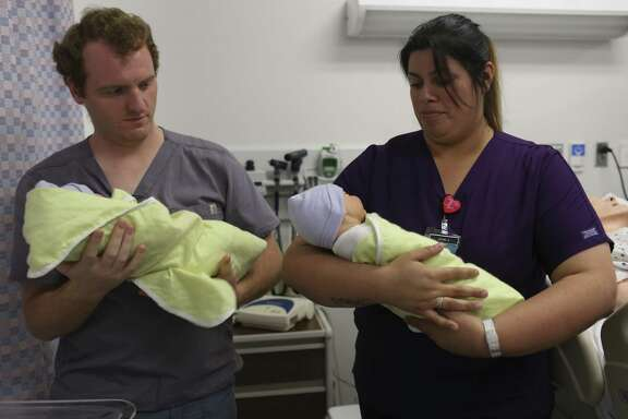 License Vocational Nurse students Norman Ryan-Waldo, left, and Ruby Cigarroa practice carrying newborns during a lab at St. Philip's College May 31, 2017. Cigarroa is a Project QUEST student. The program provides a model others should examine.