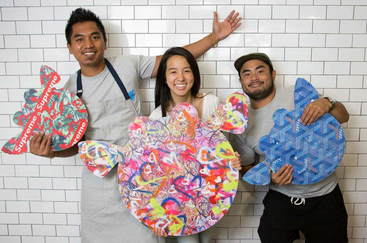 SeaSide Poke restaurant chef Vuthy Srey, left, and co-founders Kristy Nguyen and Alex Boquiren pose for a portrait with samples of artistic metal signs with their fish logo. The poke restaurant will open soon in EaDo at 2118 Lamar.