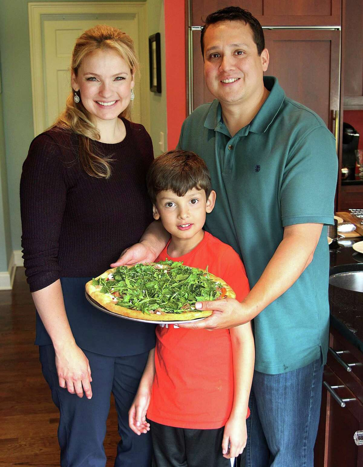 Grace, Jack and Ed Winstanley show off a freshly made goat cheese and arugula salad pizza made with PIY ingredients at a home in Ridgefield, Conn., on Wednesday, May 31, 2017.
