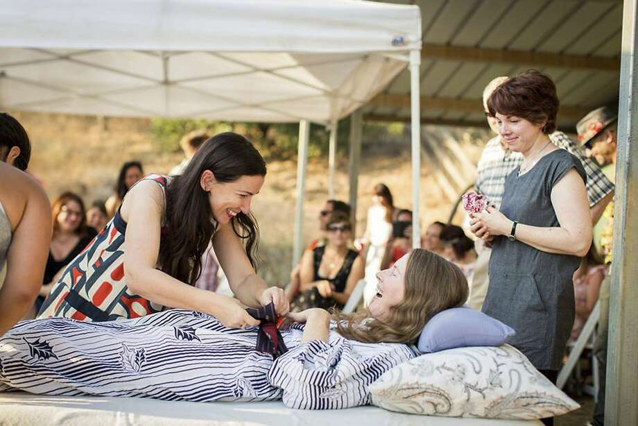"""In this Sunday, July 24, 2016 photo provided by Niels Alpert, Amanda Friedland, left, surrounded by friends and family, adjusts her friend Betsy Davis' sash as she lies on a bed during her """"Right To Die Party"""" in Ojai, Calif. At the end of the party, the 41-year-old woman diagnosed with ALS took a cocktail of lethal drugs and died, becoming one of the first California residents to take life-ending drugs under a new law that gave such an option to the terminally ill. At least 504 terminally ill Californians have requested a prescription for life-ending drugs since a state law allowing physician-assisted deaths went into effect in June 2016. (Niels Alpert via AP) Photo: Niels Alpert, Associated Press"""