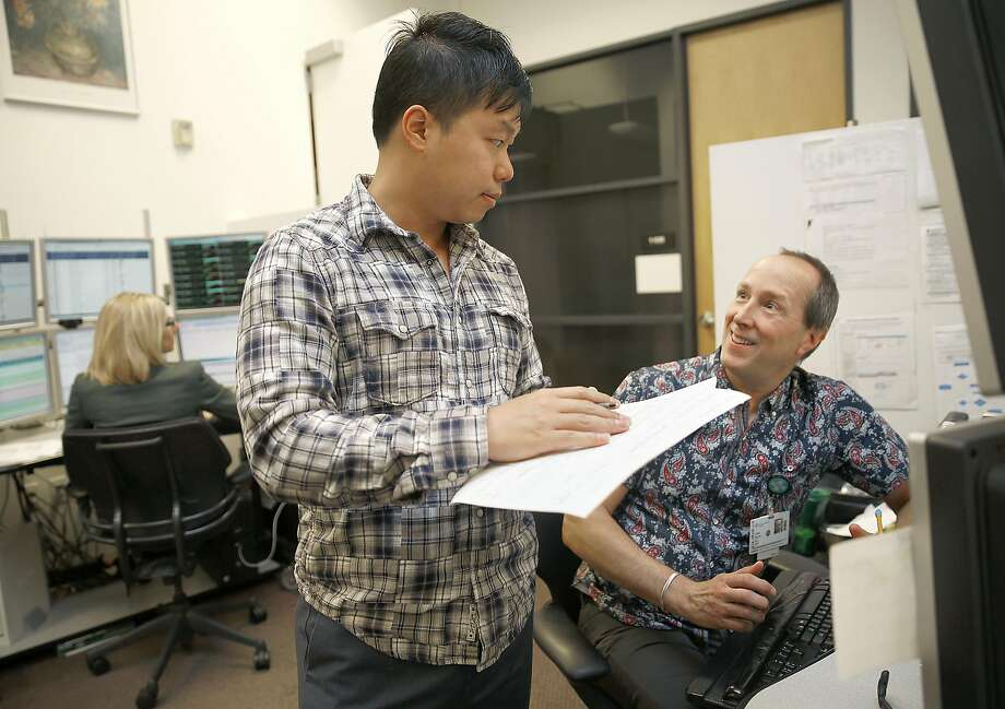 Unit coordinator Ricky Ng (left) talks with critical care nurse Clark Wurth at California Pacific Medical Center's eICU hub, where off-site ICU patients are monitored on computers. Photo: Liz Hafalia, The Chronicle
