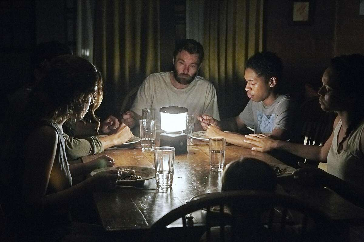 """A scene from """"It Comes at Night,"""" with Joel Edgerton, center."""